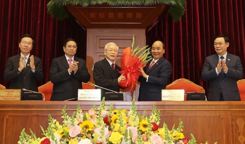 Thay mặt Bộ Chính trị, Thủ tướng Nguyễn Xuân Phúc tặng hoa chúc mừng Tổng Bí thư, Chủ tịch nước Nguyễn Phú Trọng. Ảnh: TTXVN