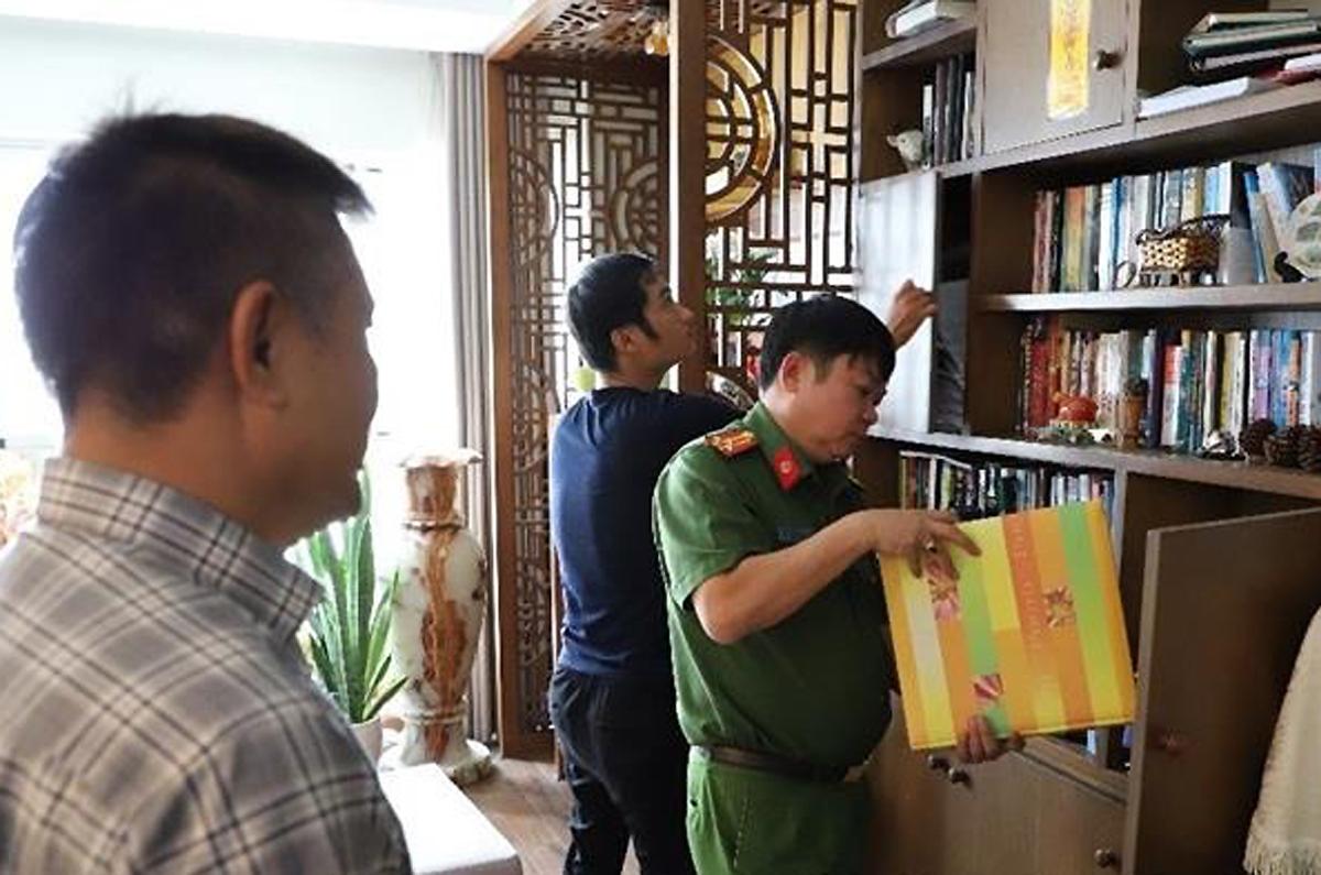 Ông Trần Huy Lập (trái) chứng kiến cơ quan điều tra khám xét. Ảnh: Công an Đồng Nai.