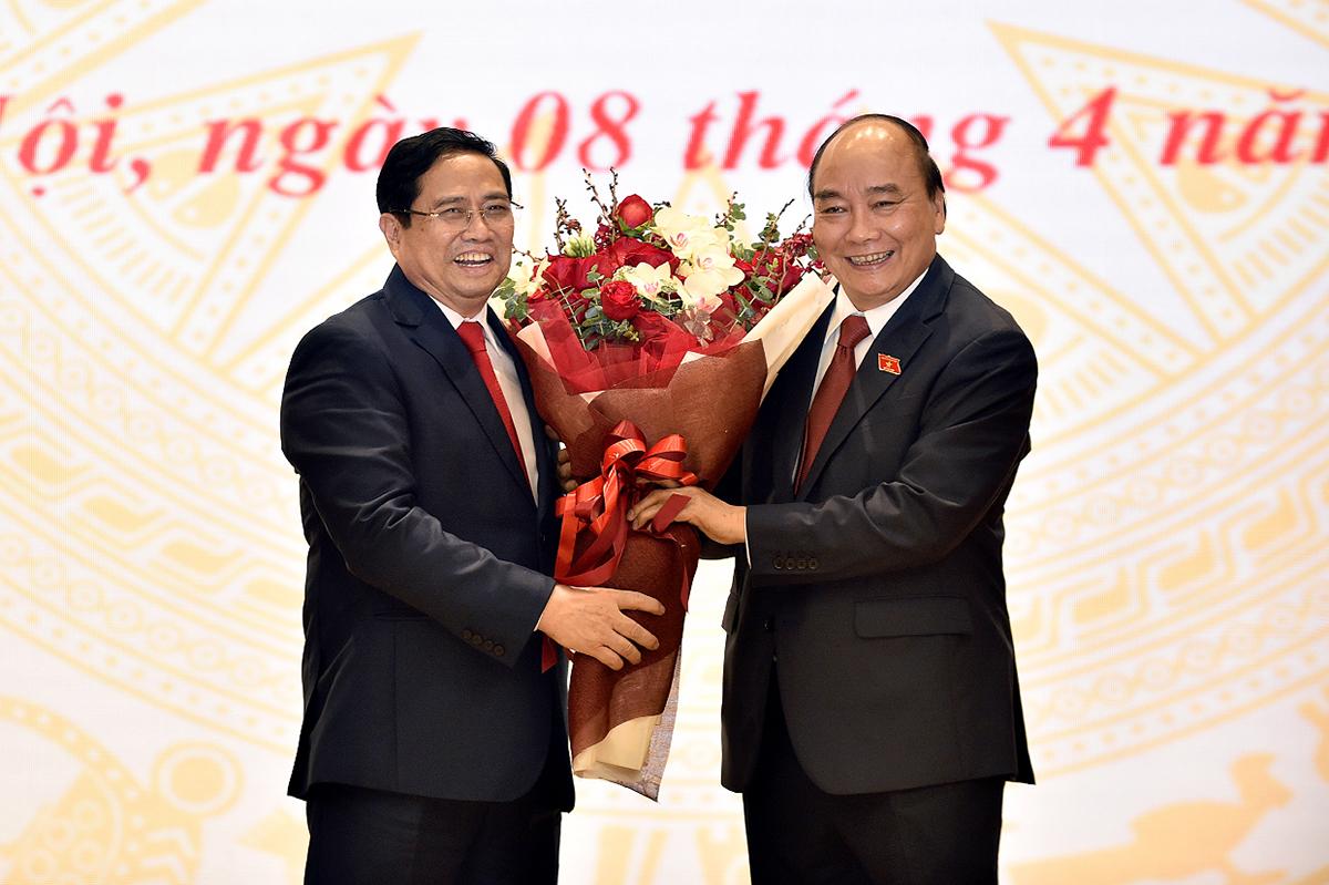Thủ tướng Phạm Minh Chính tặng hoa Chủ tịch nước Nguyễn Xuân Phúc tại lễ bàn giao công việc. Ảnh: Quang Hiếu