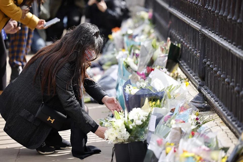 Một phụ nữ đặt hoa tưởng nhớ Hoàng thân Philip bên ngoài cung điện Buckingham hôm 9/4. Ảnh: AFP