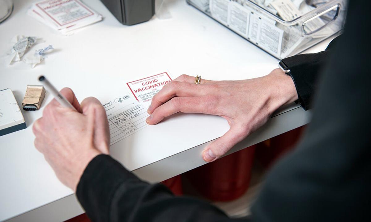 Một dược sĩ điền thông tin thẻ chứng nhận tiêm vaccine ngừa Covid-19 cho bệnh nhân tại thành phố Little Rock, bang Arkansas tháng này. Ảnh: NYTimes.