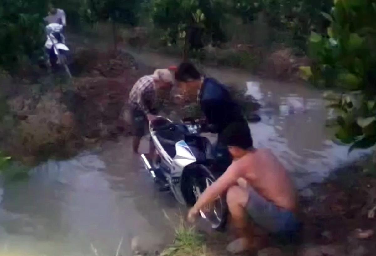 Cảnh sát thu giữ một xe máy bị nhóm đua lao xuống xuống mương để tẩu tán. Ảnh: Nam An.