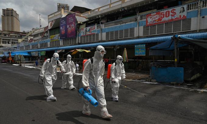 Nhân viên phòng dịch chuẩn bị phun khử trùng một khu chợ ở Phnom Penh, Campuchia, hôm 4/4. Ảnh: AFP.