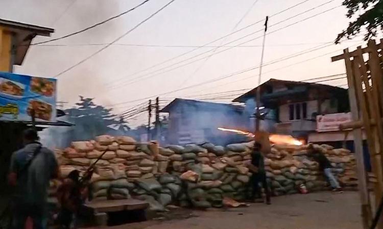 Người biểu tình cầm súng trường tự chế, nấp sau hàng rào bao cát ở thị trấn Bago, Myanmar hôm 9/4. Ảnh: AFP.
