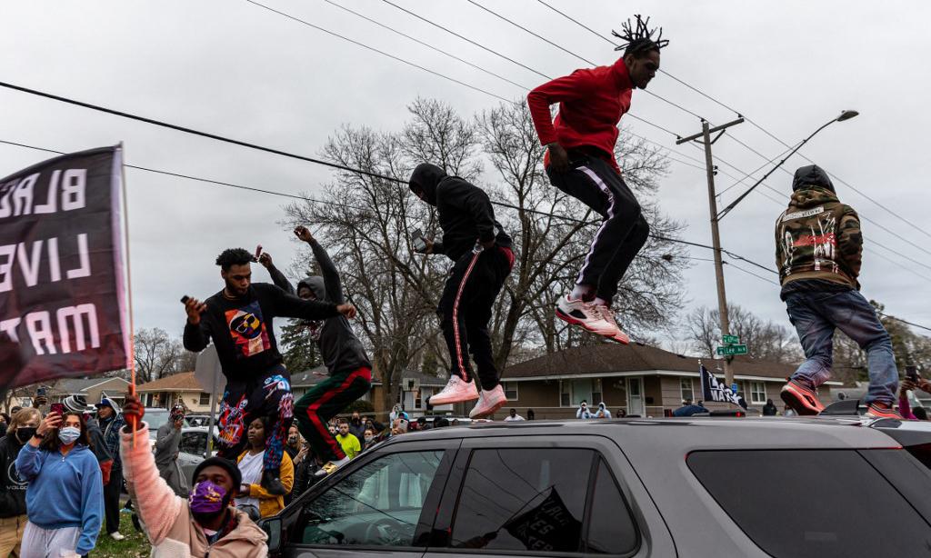 Người biểu tình nhảy lên trên một xe cảnh sát tại thành phố Brooklyn Center, bang Minneapolis, Mỹ, hôm 11/4. Ảnh: AFP.