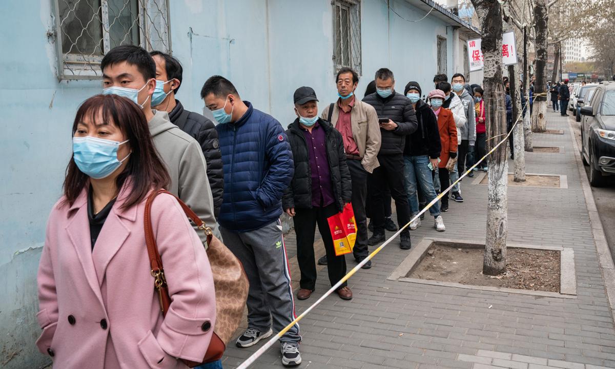 Người dân xếp hàng trước một điểm tiêm chủng ở Bắc Kinh. Ảnh: Bloomberg.