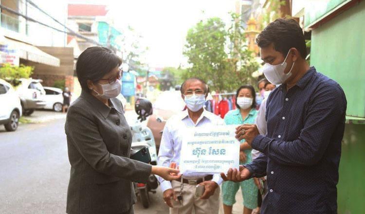 Bộ trưởng Y tế Campuchia (trái) trao phần thưởng cho Panh Savannarith (phải), người thứ một triệu tiêm vaccine Covid-19 ở Phnom Penh hôm 12//4. Ảnh: Phnom Penh Post