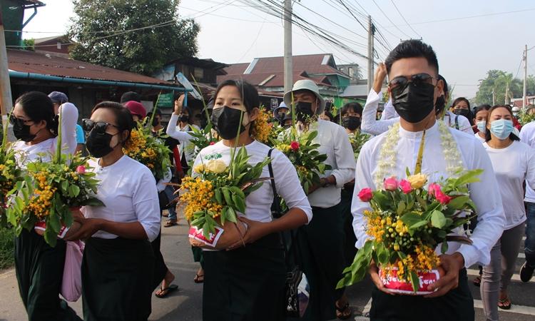 Người dân Myanmar cầm bình hoa padauk biểu tình im lặng chống đảo chính quân sự ở Dawei hôm nay. Ảnh: Reuters.
