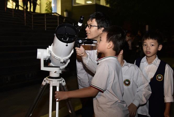 Mạnh Quân hướng dẫn các em nhỏ sử dụng kính thiên văn. Ảnh: Nhân vật cung cấp