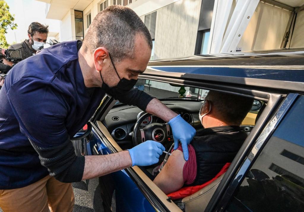 Y tá tiêm vaccine Pfizer-BioNTech cho một người ngồi trên xe ở Pháp ngày 13/4. Ảnh: AFP.