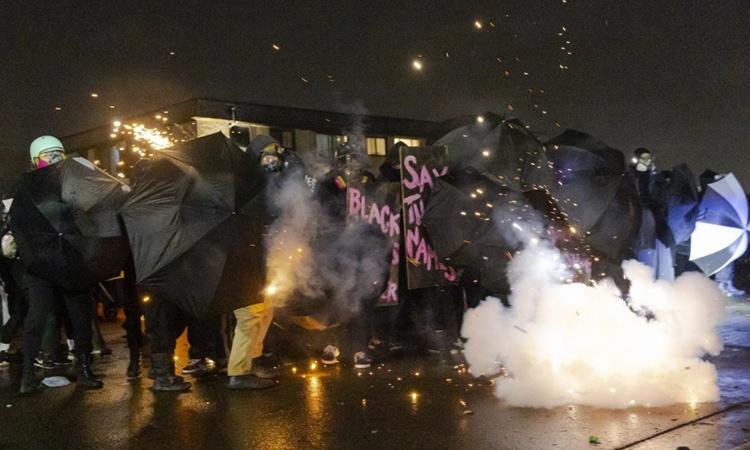 Đám đông biểu tình dùng ô chống đạn hơi cay của cảnh sát ở Brooklyn Center, Minnesota, đêm 13/4. Ảnh: AFP.