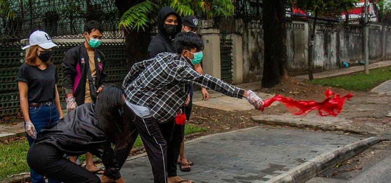 Người biểu tình đổ sơn đỏ ra đường phố ở Yangon. Ảnh: AP.