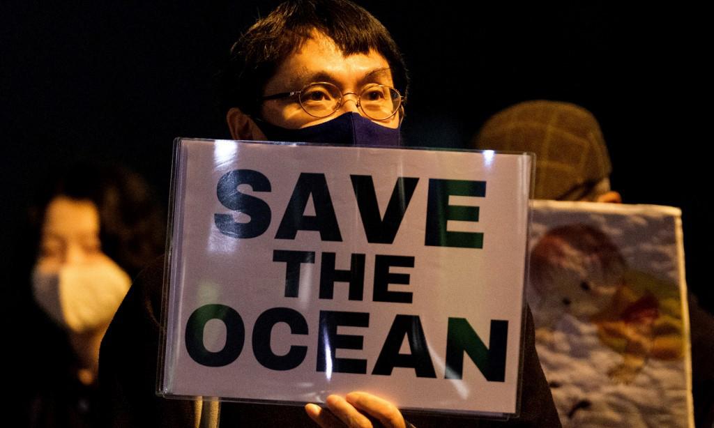 Người biểu tình cầm khẩu hiệu Bảo vệ Đại dương bên ngoài văn phòng Thủ tướng Nhật ở Tokyo hôm 13/4, nhằm phản đối quyết định xả nước thải nhà máy Fukushima ra biển. Ảnh: AFP.