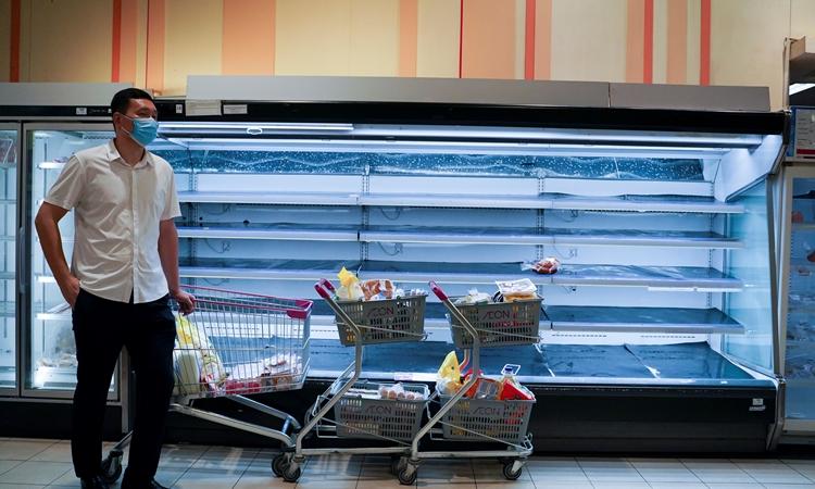 Người đàn ông với xe hàng chất đầy đồ đứng trước một quầy đồ đông lạnh trống trơn trong siêu thị ở thủ đô Phnom Penh, Campuchia, hôm 14/4. Ảnh: Reuters.