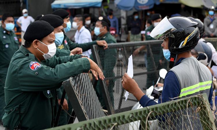 Cảnh sát chặn những người đi xe máy qua một trạm kiểm soát được thiết lập giữa thủ đô Phnom Penh và thị xã Ta Khmao ở tỉnh lân cận Kandal hôm nay. Ảnh: AFP.