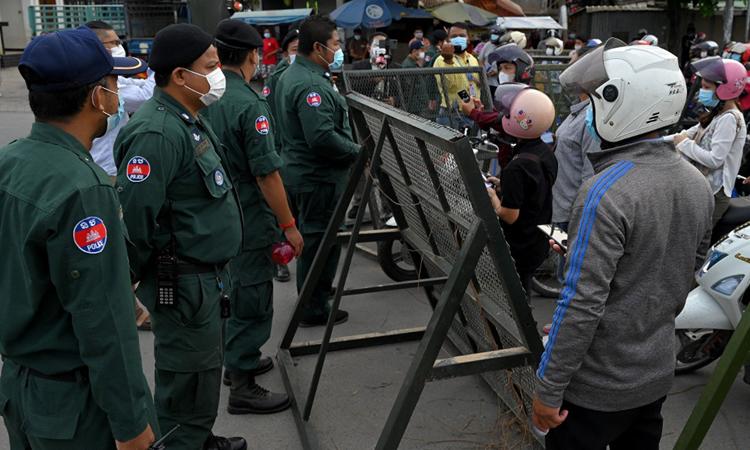 Cảnh sát chặn người đi xe máy tại một trạm kiểm soát ở thủ đô Phnom Penh, Campuchia hôm nay. Ảnh: AFP.