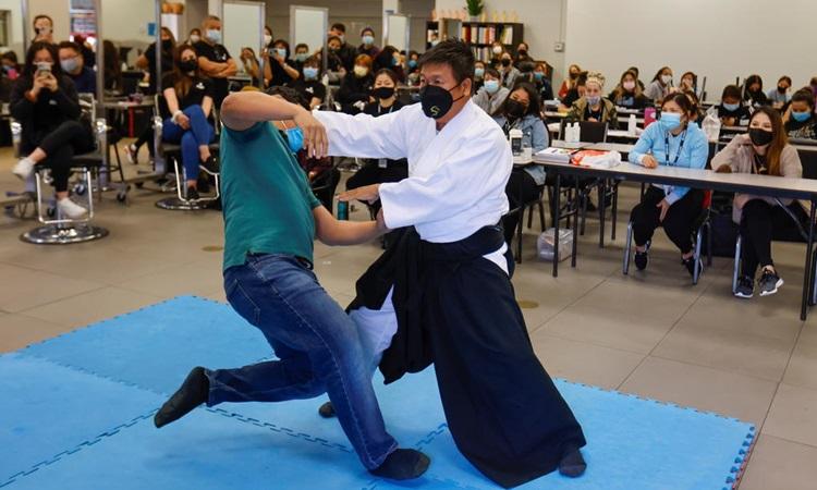 Huấn luyện viên Aikido đai đen Tam Ha dạy cách tự vệ cho học viên trường Advance Beauty College ở thành phố Garden Grove, California, Mỹ hôm 12/4. Ảnh: Reuters.