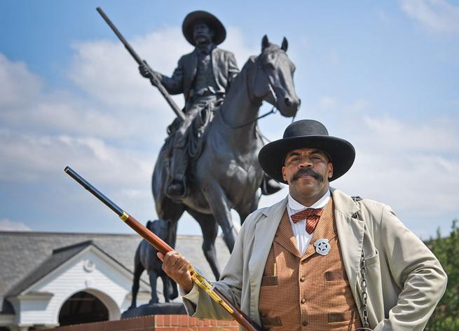 Một người đàn ông đứng trước bức tượng đồng cao 7,5 m khắc họa Bass Reeves. Ảnh: Living in Arkansas/Mauren Kennedy.
