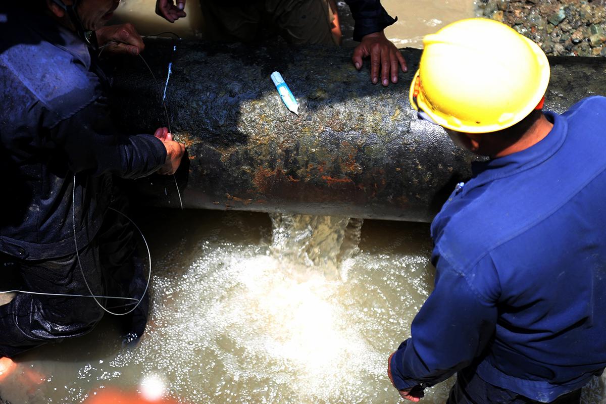 Đường ống gang bị vỡ được công nhân đo đạc để thay thế ống mới. Ảnh: Đình Văn.