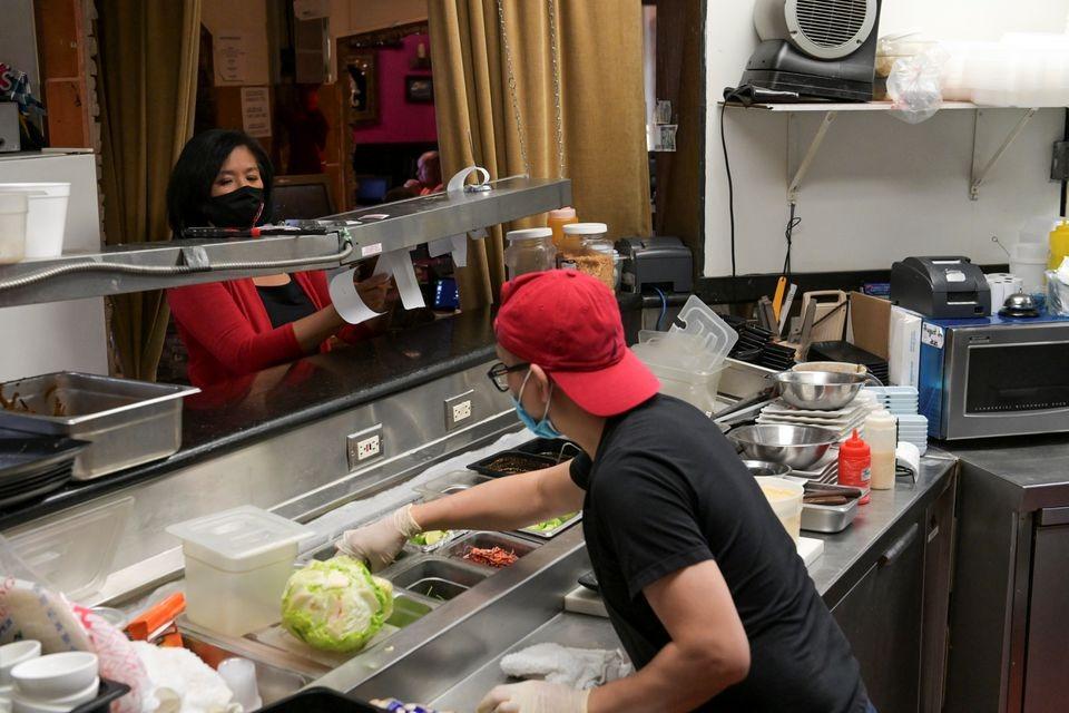 Jan-le Low, (trái) dịch chuyển đơn đặt hàng trong khi nhân viên làm món cho khách tại nhà hàng Satay ở Las Vegas, bang Nevada, Mỹ, hôm 28/3. Ảnh: Reuters