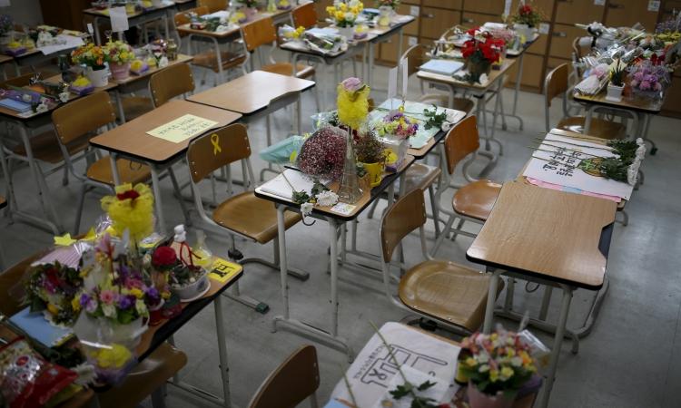 Hoa và kỷ vật được đặt trên bàn của các học sinh trường Danwon thiệt mạng trong vụ chìm phà Sewol. Ảnh: Reuters.