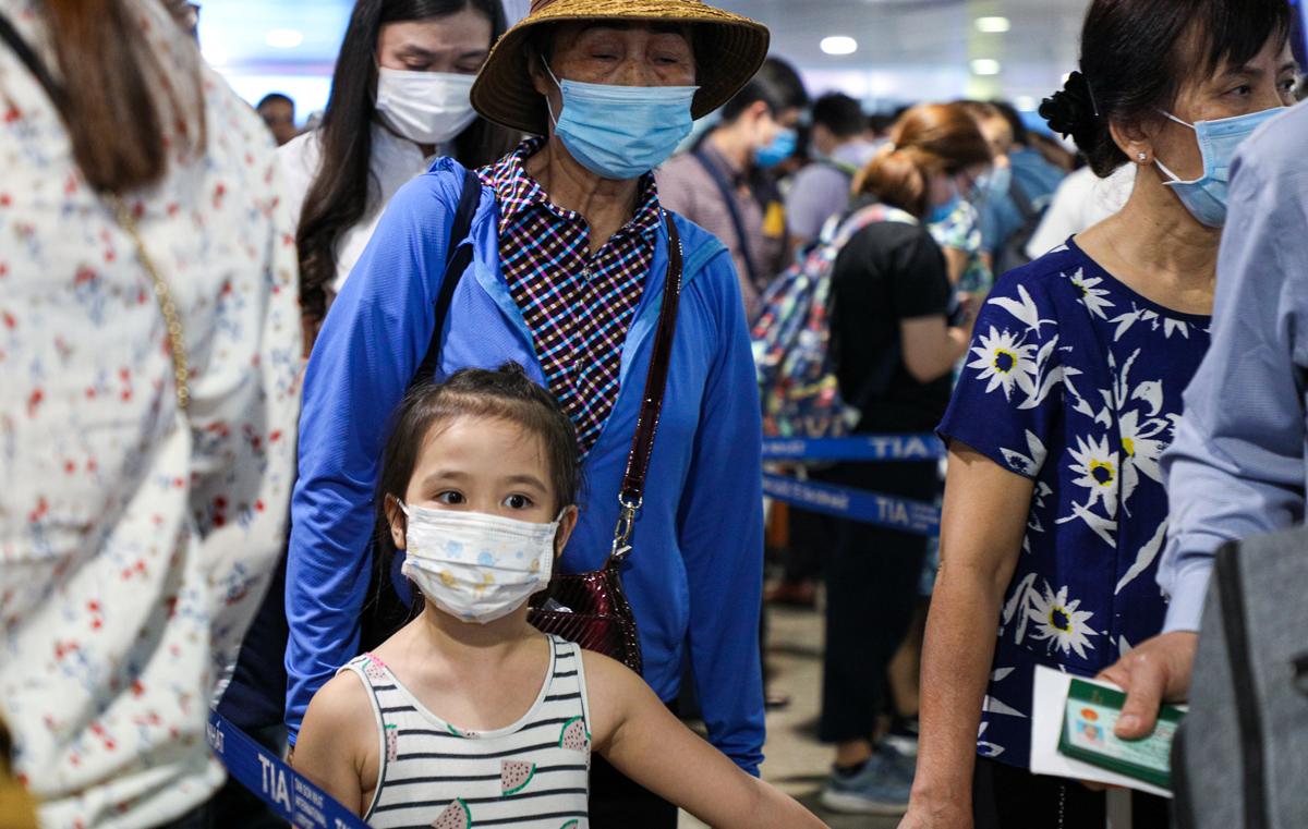 Người già, trẻ em xếp hàng chờ kiểm tra an ninh tại sân bay Tân Sơn Nhất sáng 16/4. Ảnh: Gia Minh.