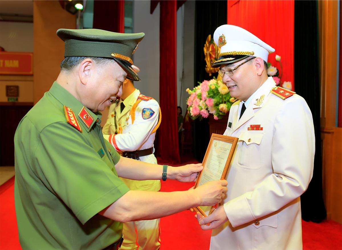 Bộ trưởng Tô Lâm trao quyết định thăng quân hàm cho trung tướng Tô Ân Xô chiều 16/4. Ảnh: Bộ Công an