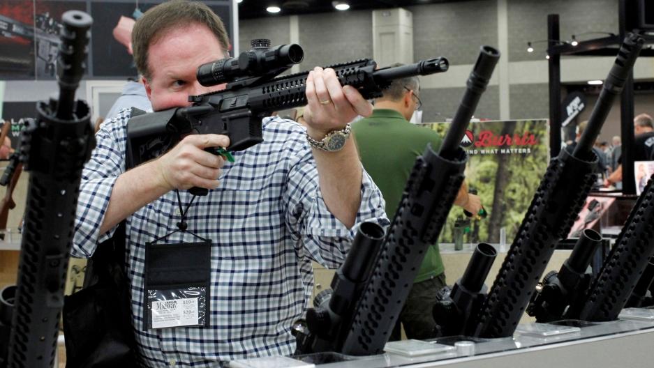 Một khách tham quan kiểm tra súng tại triển lãm vũ khí thường niên ở Louisville, Kentucky, năm 2016. Ảnh: Reuters.