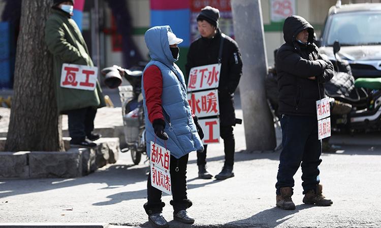 Người lao động mang biển quảng cáo kỹ năng tìm việc làm ở Thẩm Dương hồi tháng 2. Ảnh: AFP.