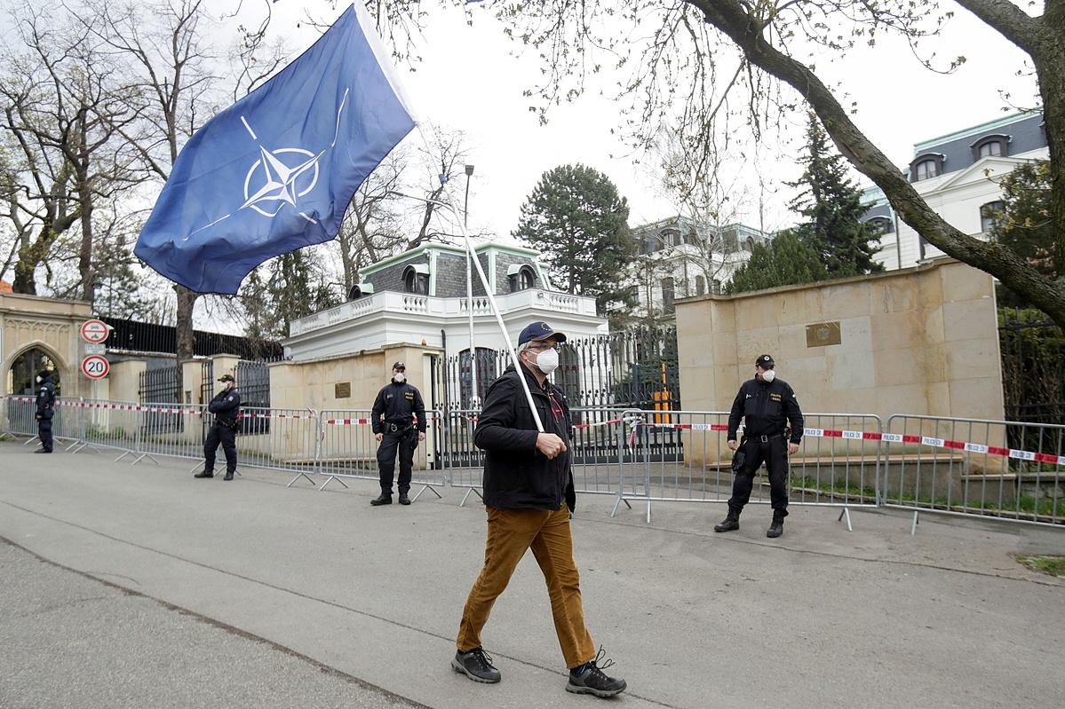 Một người cầm cờ NATO phản đối Nga ngoài đại sứ quán Nga tại Prague, Czech, hôm 18/4. Ảnh: Reuters