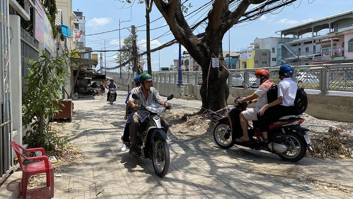 Trễ hạn 9 tháng nhưng đường dân sinh hai bên chân cầu Quang Trung (cửa ngõ Cần Thơ) chưa được xây dựng, khiến người dân chạy xe trên vỉa hè. Ảnh: Cửu Long