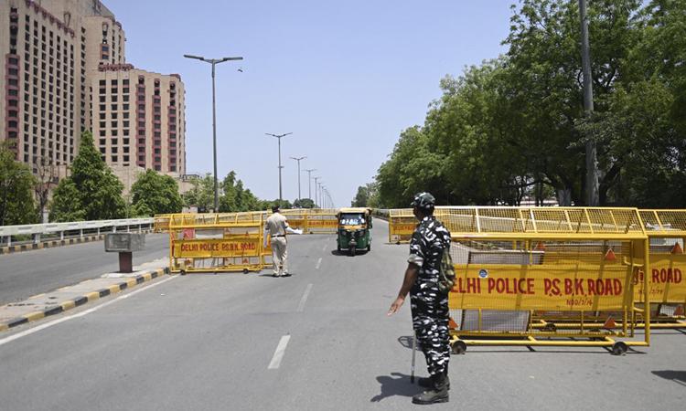 Cảnh sát dừng một phương tiện tại chốt kiểm soát Covid-19 ở thủ đô New Delhi, Ấn Độ hôm 18/4. Ảnh: AFP.