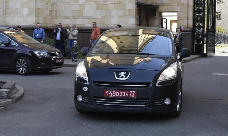 Xe chở nhà ngoại giao Czech rời đại sứ quán ở Moskva hôm 19/4. Ảnh: AFP.