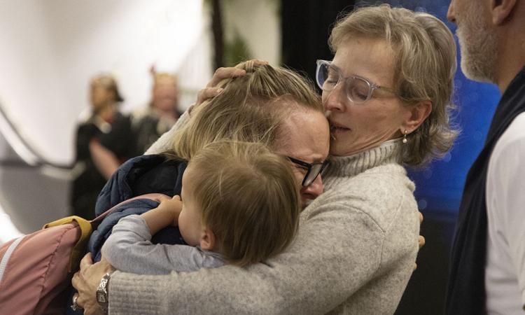 Một gia đình được đoàn tụ ở Weallington, New Zealand hôm nay sau khi chuyến bay đầu tiên chở người về từ Sydney, Australia hạ cánh. Ảnh: AFP.