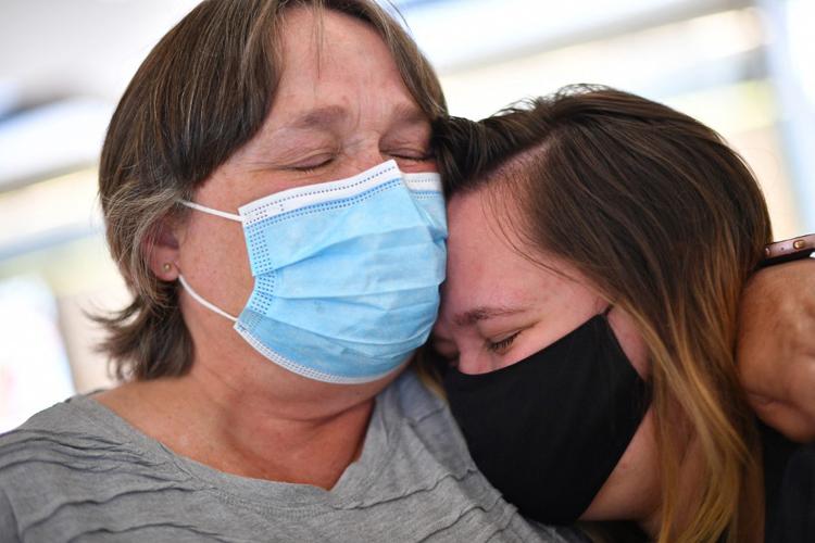 Một người mẹ (trái) ôm con gái tại Sân bay Quốc tế Sydney, Australia hôm nay sau khi cô trở về từ New Zealand. Ảnh: AFP.