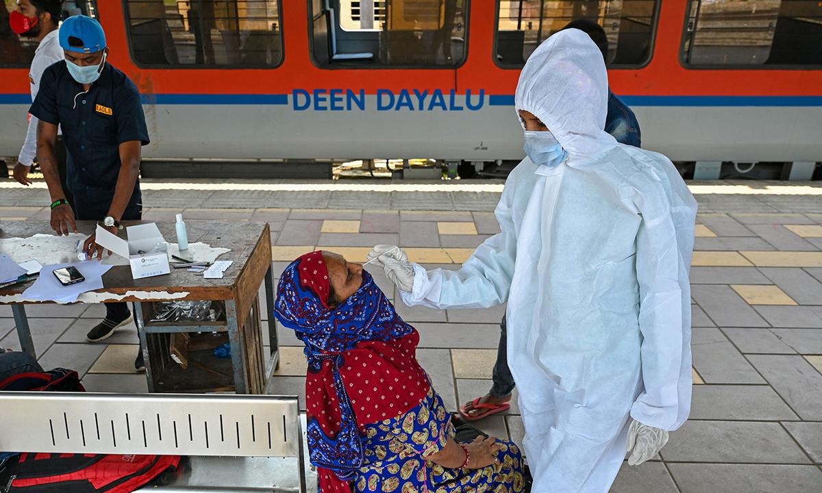 Nhân viên y tế lấy mẫu xét nghiệm Covid-19 cho hành khách tại ga tàu ở Mumbai, Ấn Độ hôm 14/4. Ảnh: AFP.
