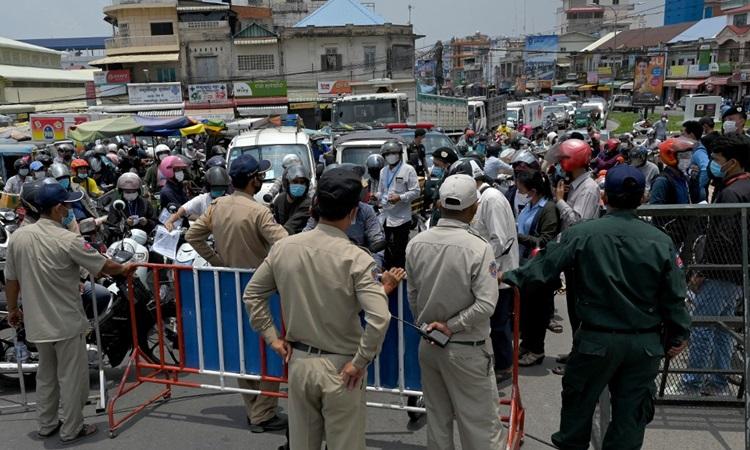 Cảnh sát Campuchia chặn các phương tiện đi qua một chốt kiểm dịch Covid-19 ở thủ đô Phnom Penh hôm 17/4. Ảnh: AFP.