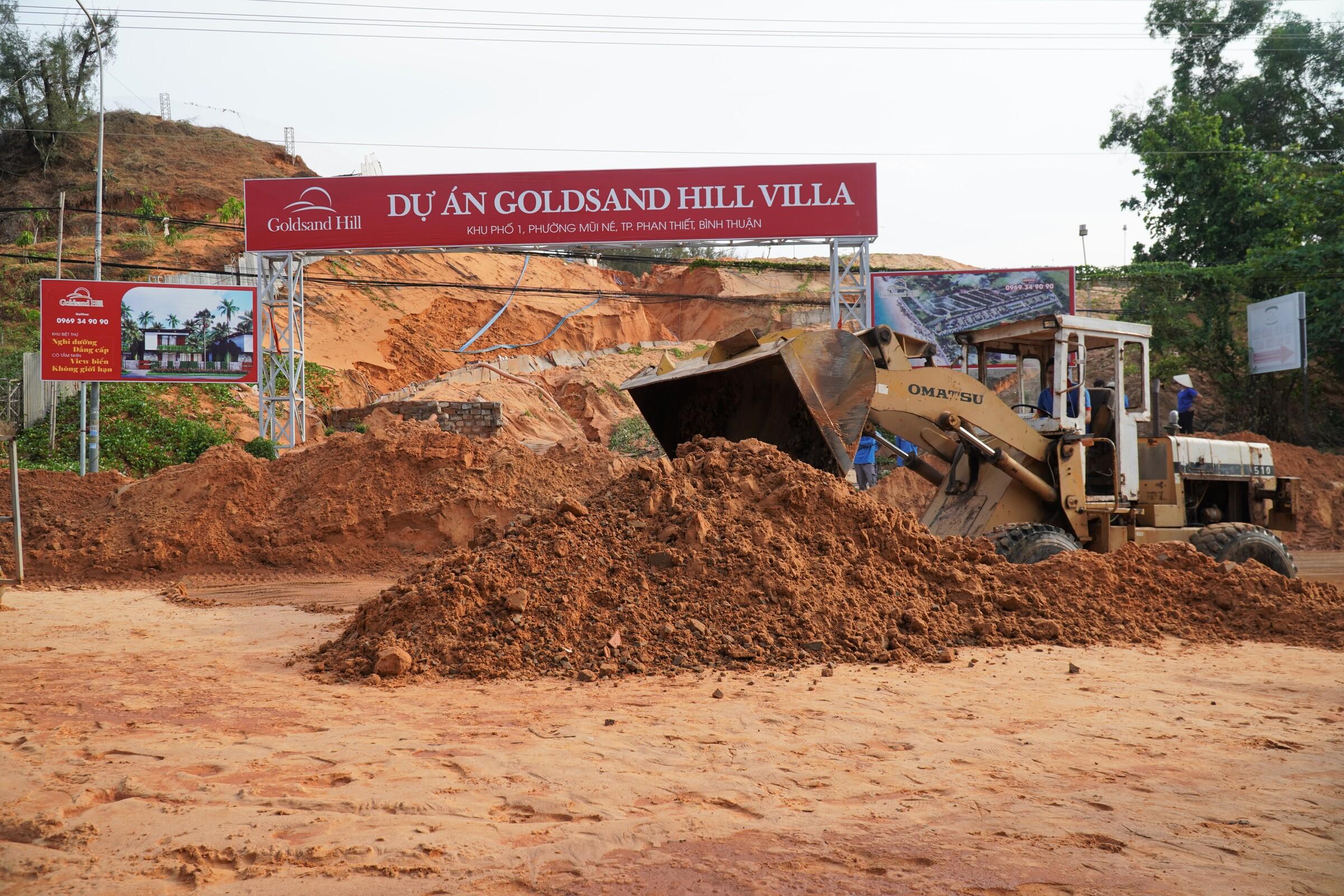 Xe xúc đang ủi cát, dọn dẹp lượng cát tràn xuống đường Huỳnh Thúc Kháng. Ảnh: Việt Quốc.
