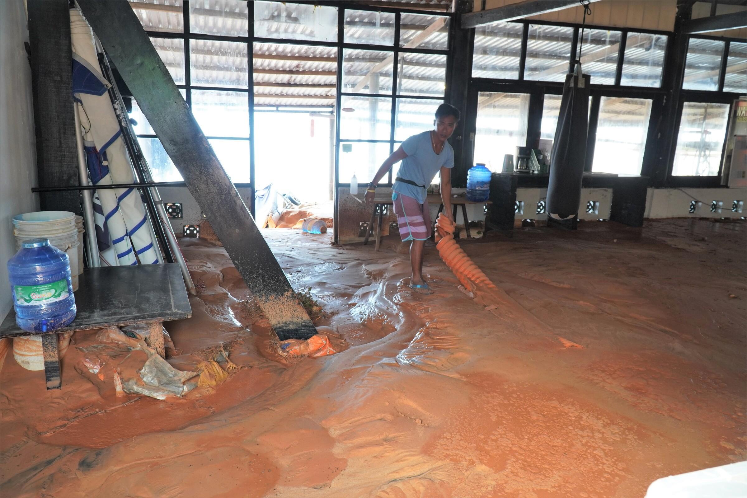 Anh Phụng đang dọn dẹp lại hiện trường do lũ cát tràn vào nhà, sáng 21/4. Ảnh: Việt Quốc.