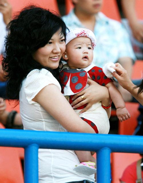 Vương Thị ôm con trong một trận bóng đá trước khi bị tuyên án vào năm 2013. Ảnh: AFP.