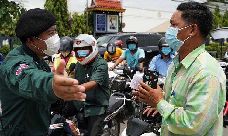 Một sĩ quan cảnh sát Campuchia kiểm tra giấy tờ của người dân tại trạm kiểm soát ở thủ đô Phnom Penh hôm 16/4. Ảnh: Reuters.