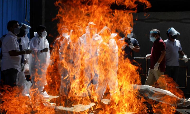 Người thân mặc đồ bảo hộ dự lễ hỏa táng một người đàn ông chết vì Covid-19 tại New Delhi, Ấn Độ hôm 21/4. Ảnh: Reuters.