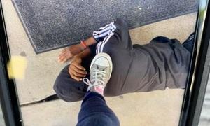 Cô giáo Mỹ đè chân lên gáy cậu bé da màu