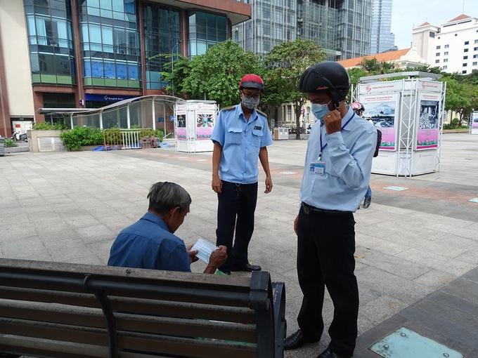 Một người dân ngồi ở phố đi bộ Nguyễn Huệ, quận 1, không đeo khẩu trang bị cơ quan chức năng nhắc nhở, hồi tháng 8/2020. Ảnh:Hà An.
