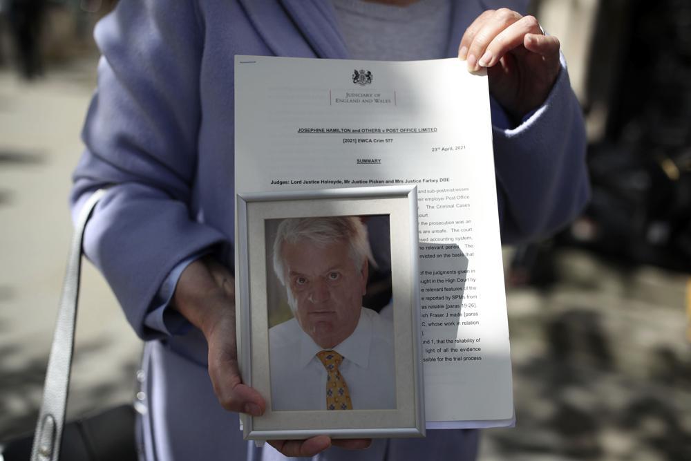 Cựu trưởng bưu cục Julian Wilson chết vào năm 2016. Di ảnh của ông được vợ cầm bên ngoài tòa nhà Tòa án Tư pháp Hoàng gia tại London vào ngày 23/4/2021. Ảnh: AP.