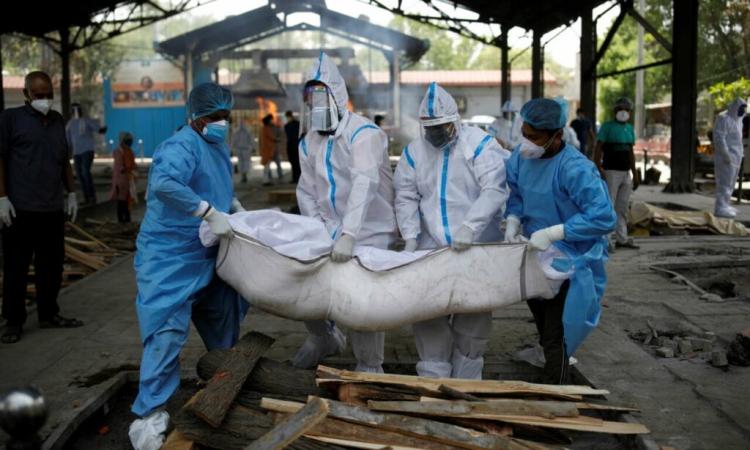 Nhân viên y tế cùng người thân khiêng thi thể một bệnh nhân Covid-19 lên giàn thiêu ở thủ đô New Delhi, Ấn Độ, hôm 21/4. Ảnh: Reuters.