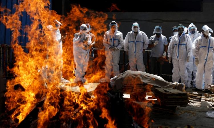 Thân nhân mặc đồ bảo hộ cá nhân đứng bên giàn hỏa táng của một người đàn ông tử vong do Covid-19 ở New Delhi, Ấn Độ, hôm 21/4. Ảnh: Reuters.