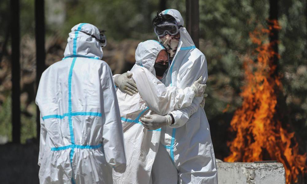 Gia đình của một nạn nhân chết vì Covid-19 trong lễ hỏa táng tại thành phố Jammu, Ấn Độ, hôm 25/4. Ảnh: AP.