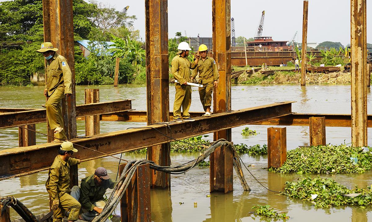 Sau khi cần cẩu cắm các dầm thép xuống lòng kênh, công nhân dùng hàn cố định làm khung đập ngăn mặn. Ảnh: Hoàng Nam