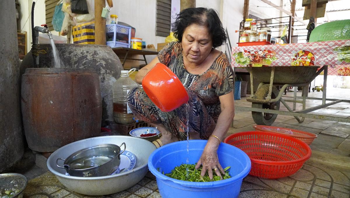 Bà Lê Thị Diệu sử dụng nước tiết kiệm để nấu ăn vì lo giá nước tăng cao ảnh hướng đến đời sống. Ảnh: Hoàng Nam